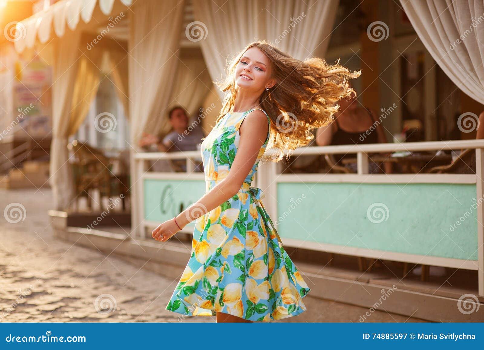 Mulher bonita feliz com cabelo longo lisonjeiramente no st do verão