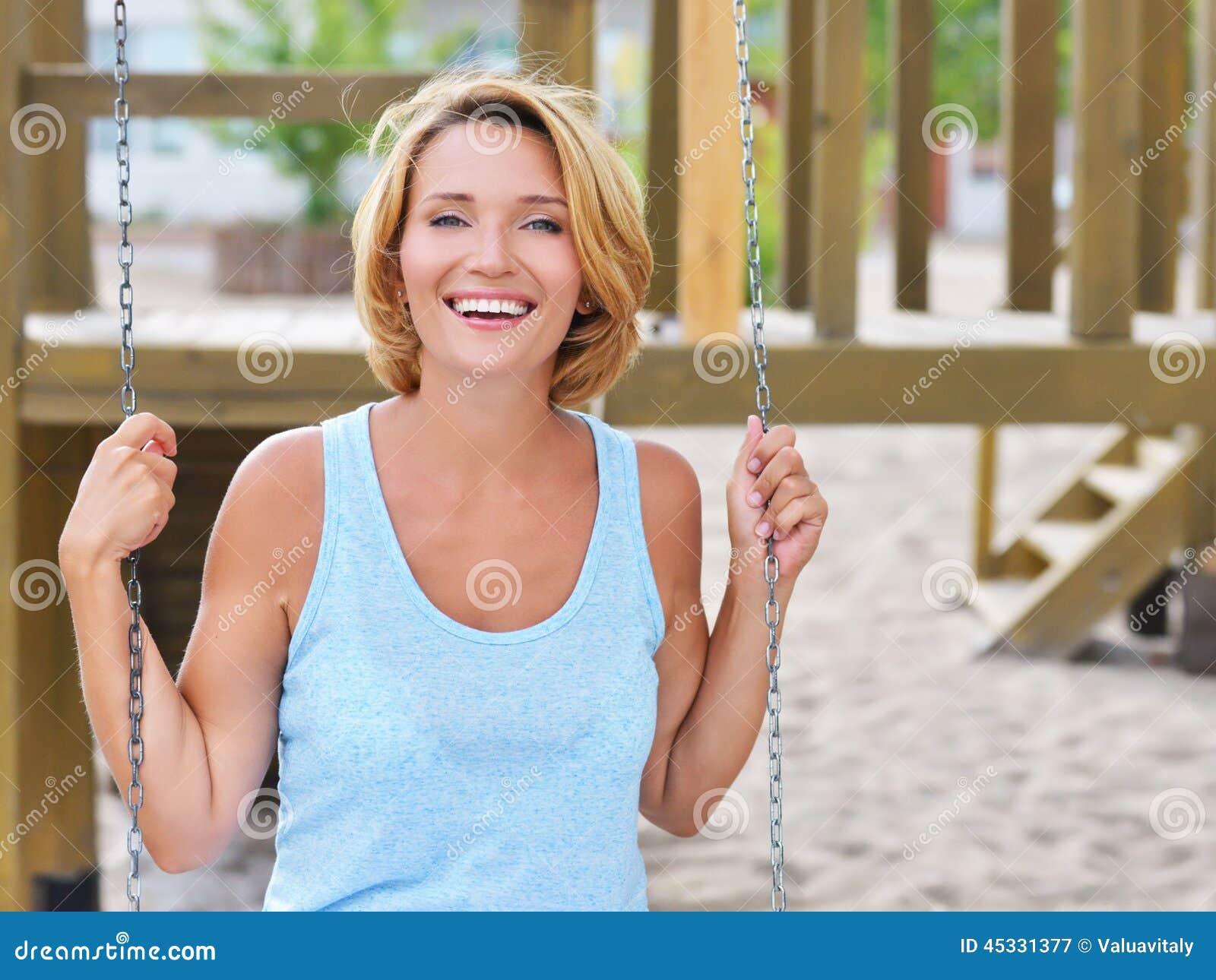 Mulher bonita feliz que tem o divertimento em um balanço