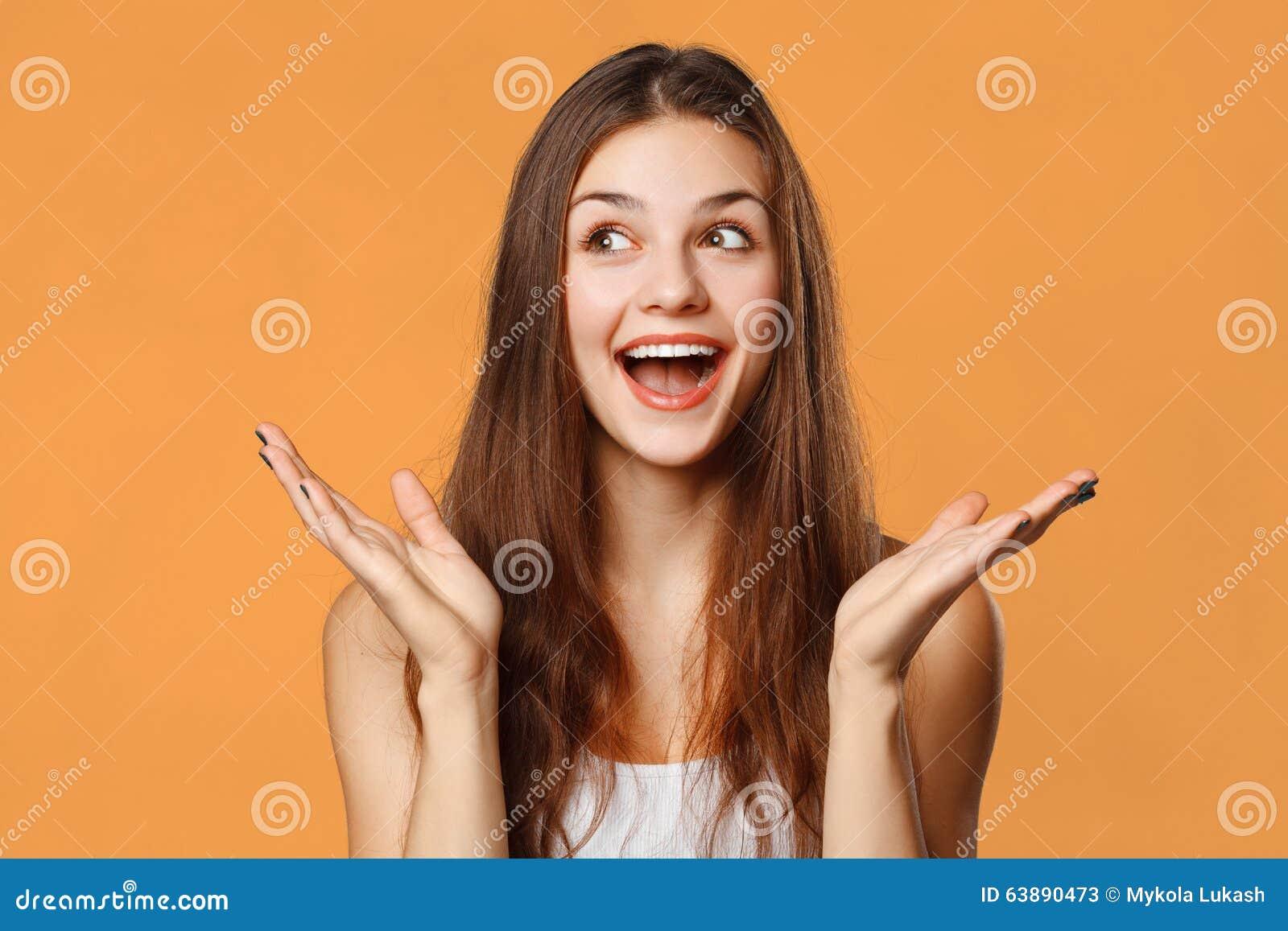 Mulher bonita feliz surpreendida que olha lateralmente no excitamento Isolado no fundo alaranjado