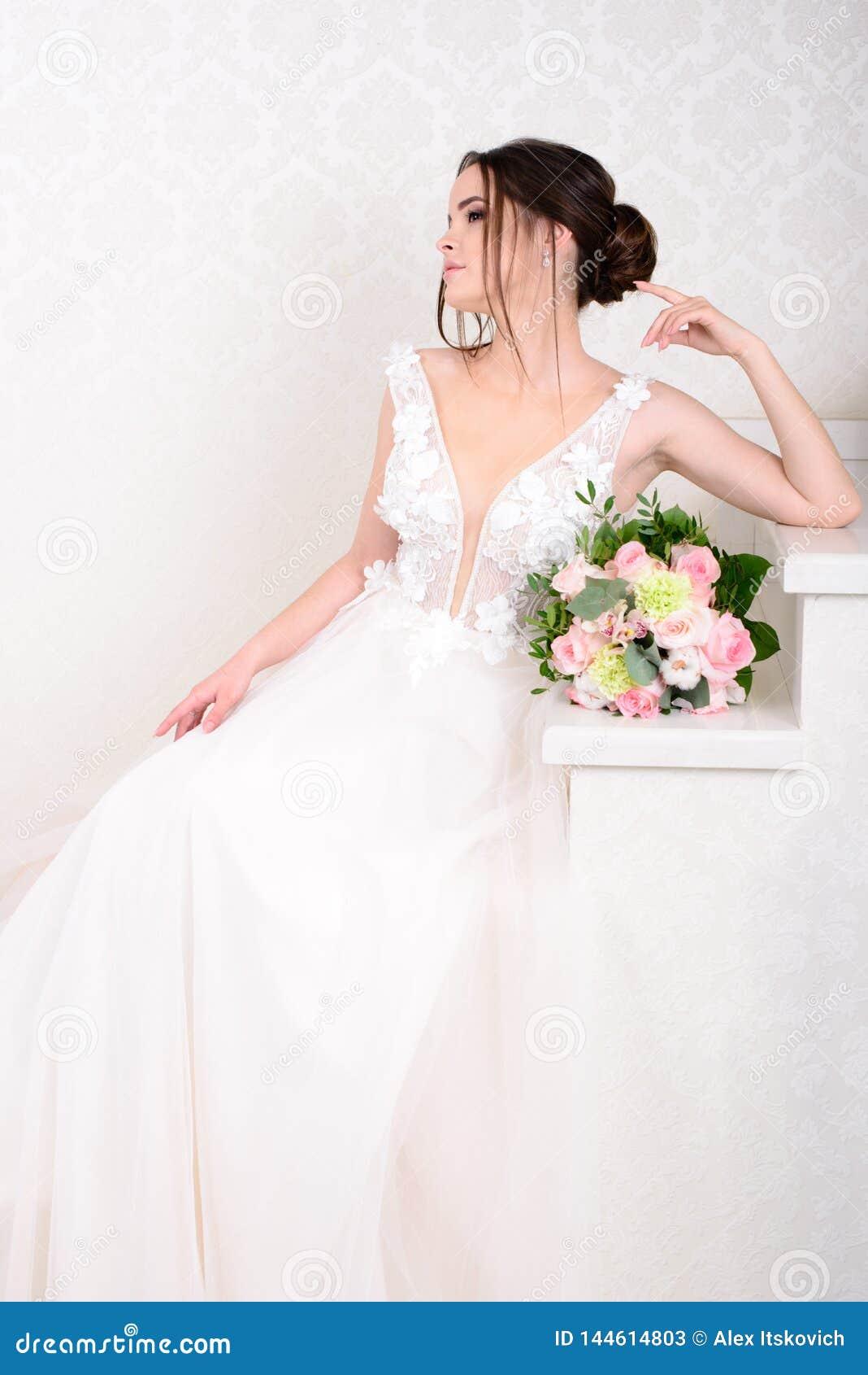 Mulher bonita magro que veste o vestido de casamento luxuoso sobre o fundo branco do est?dio Noiva lindo que guarda flores