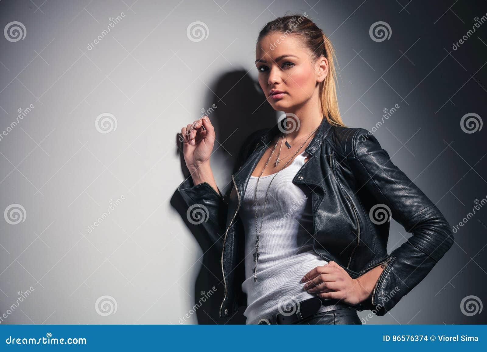 Mulher bonita na roupa de couro que inclina-se na parede cinzenta