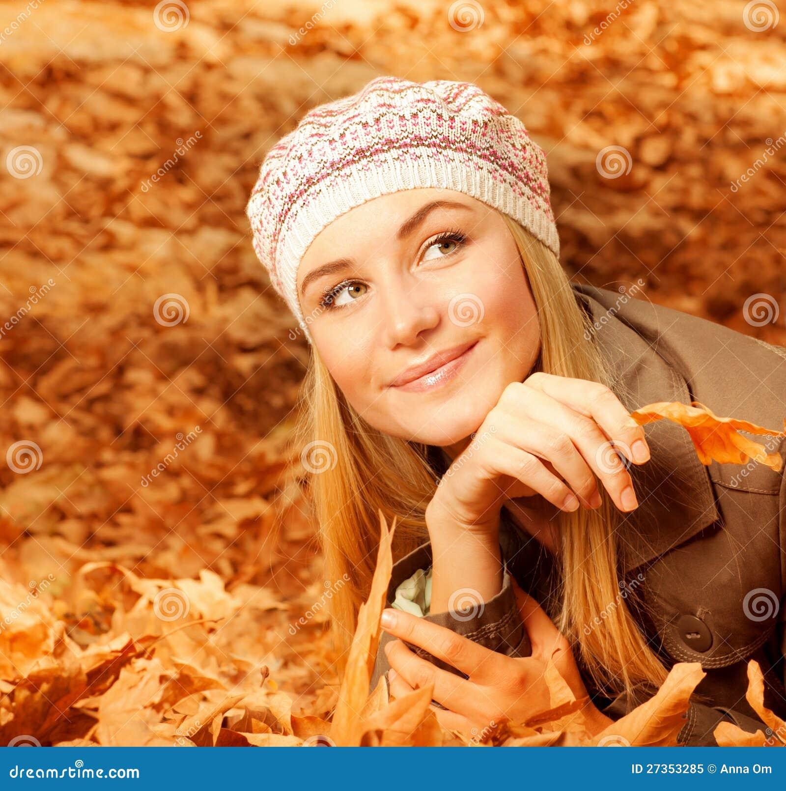 Mulher bonita nas folhas outonais