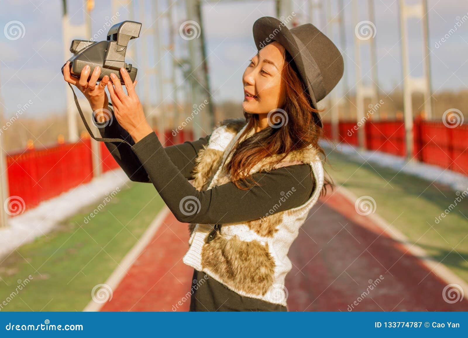 A mulher bonita no chapéu negro faz um selfie polaroid em uma ponte no inverno em Europa