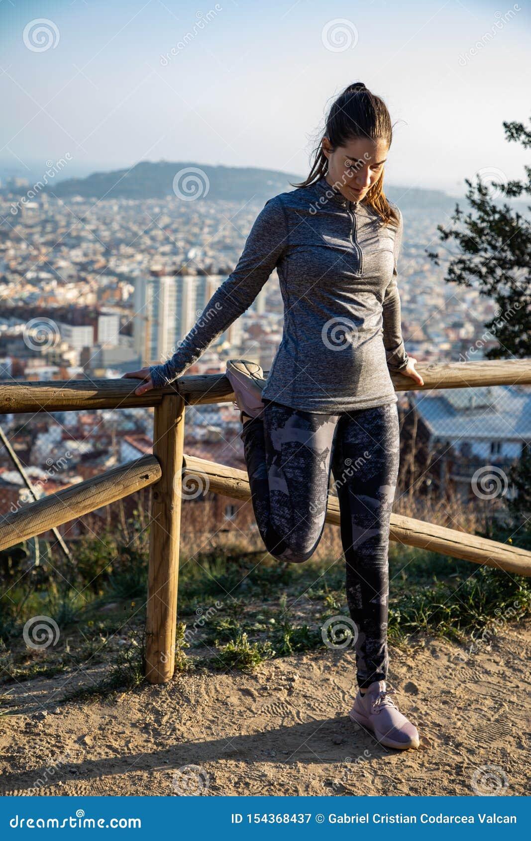 A mulher bonita no equipamento do esporte que estica no parque com a cidade de Barcelona borrou no fundo