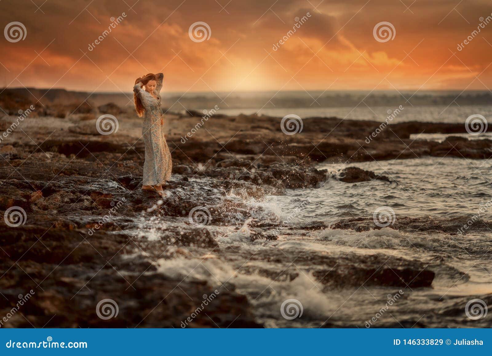 Mulher bonita no litoral das rochas no nascer do sol