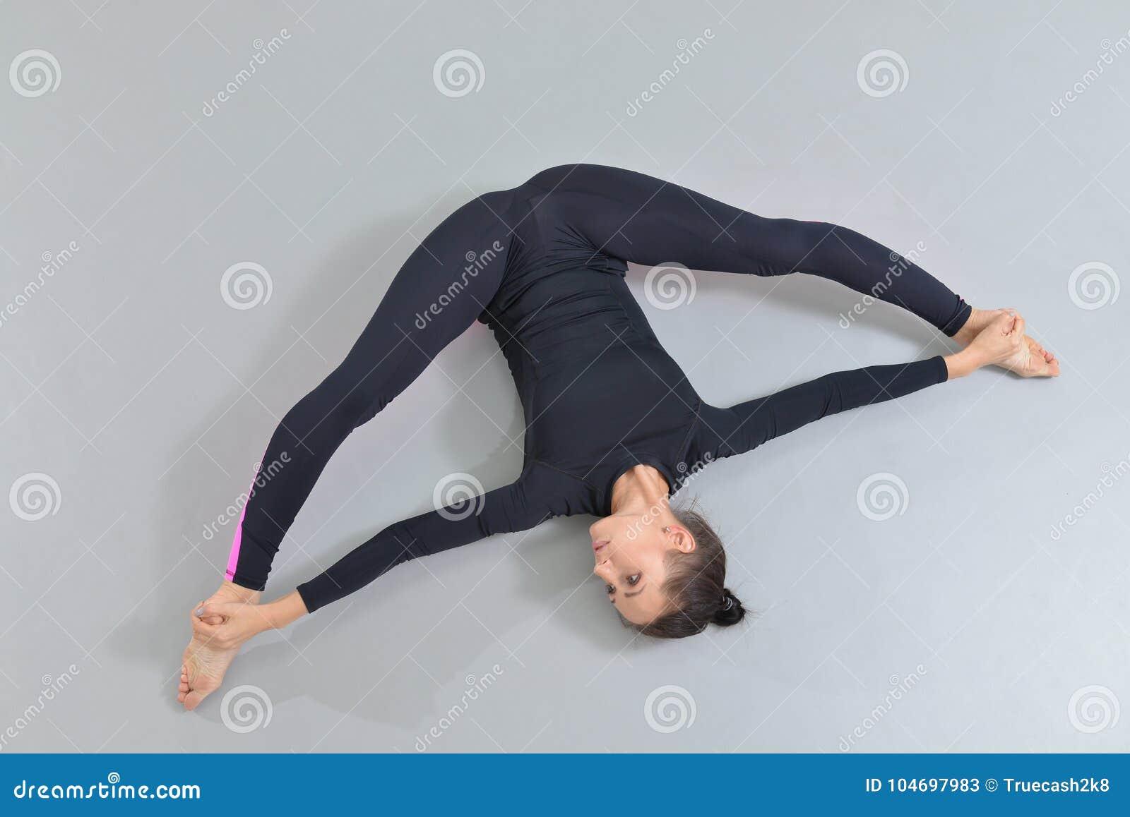 Mulher bonita no sportswear que exercita no estúdio da aptidão, executando a guita que encontra-se no assoalho Opinião de ângulo