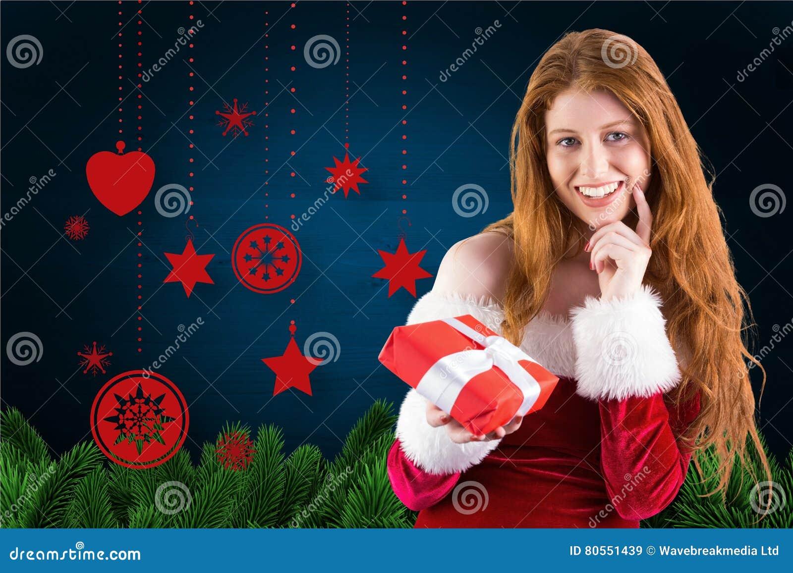 Mulher bonita no traje de Santa que guarda um presente do Natal