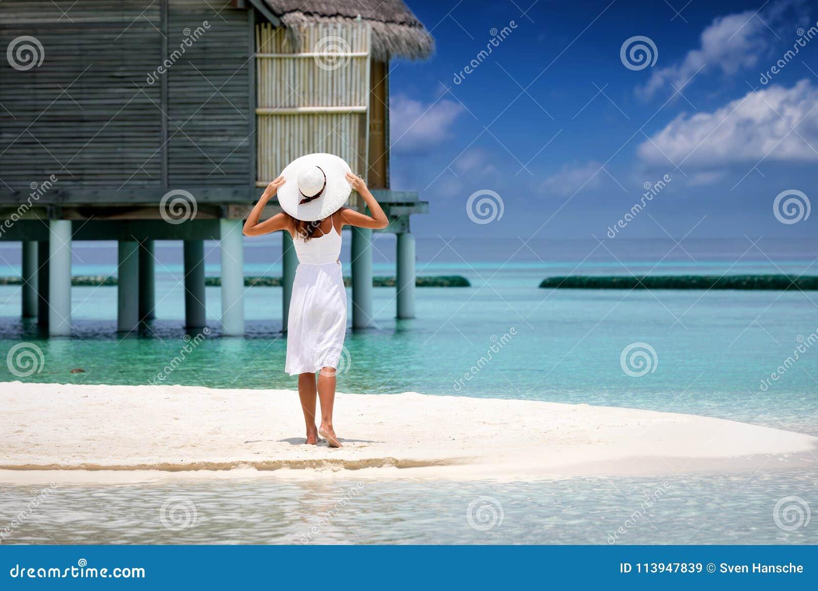 A mulher bonita no vestido branco está em uma praia em Maldivas