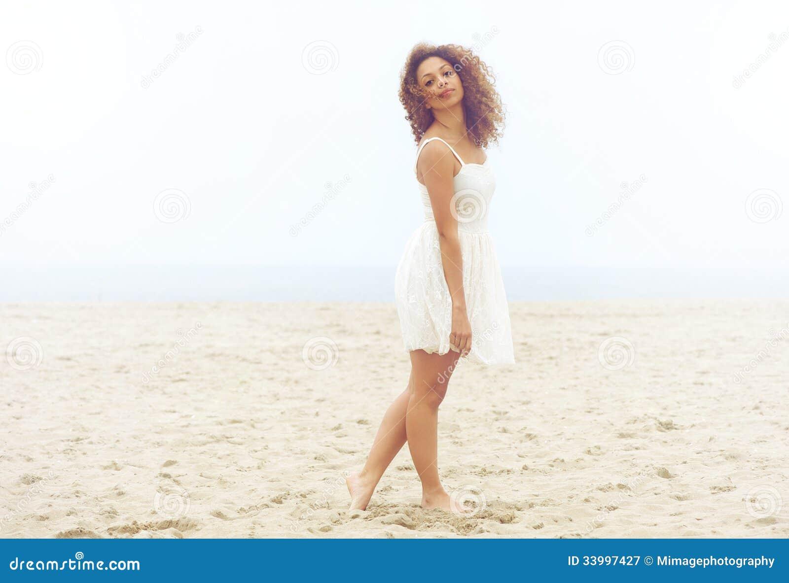 Mulher bonita no vestido branco que anda na areia na praia