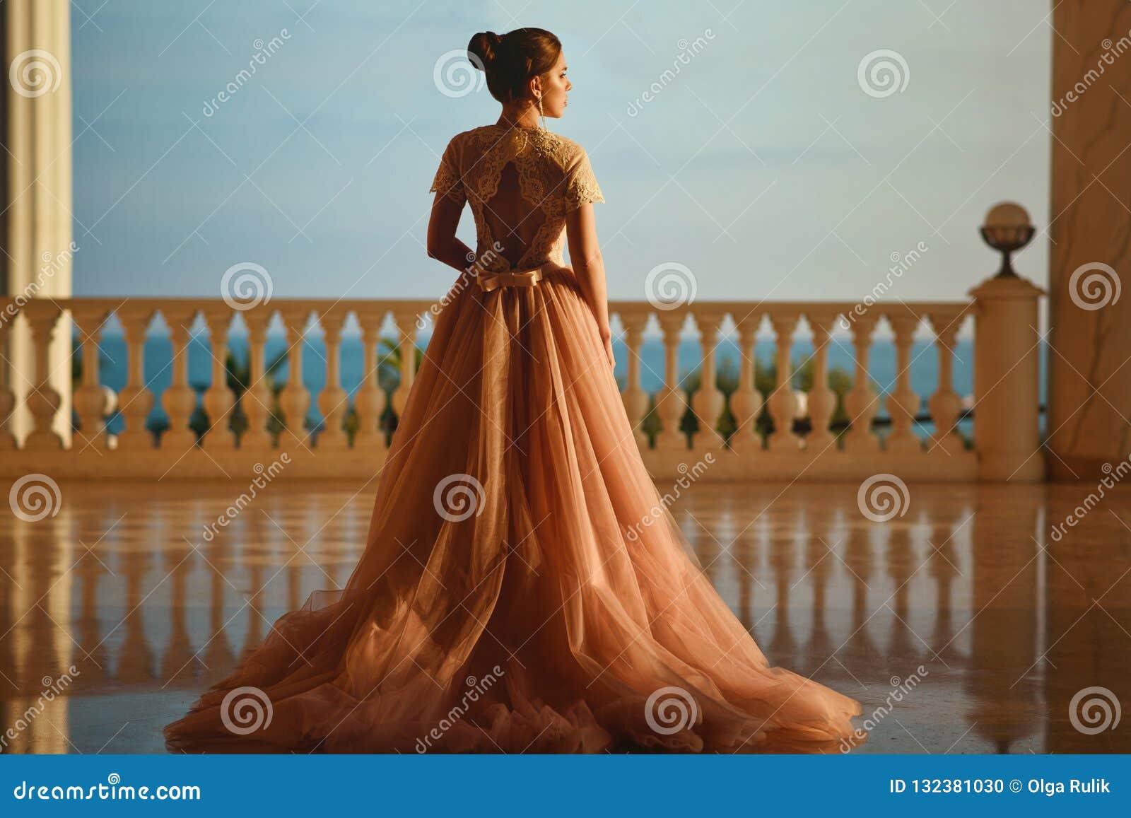 Mulher bonita no vestido luxuoso do salão de baile com saia do tule e posição superior laçado no grande balcão com opinião do mar
