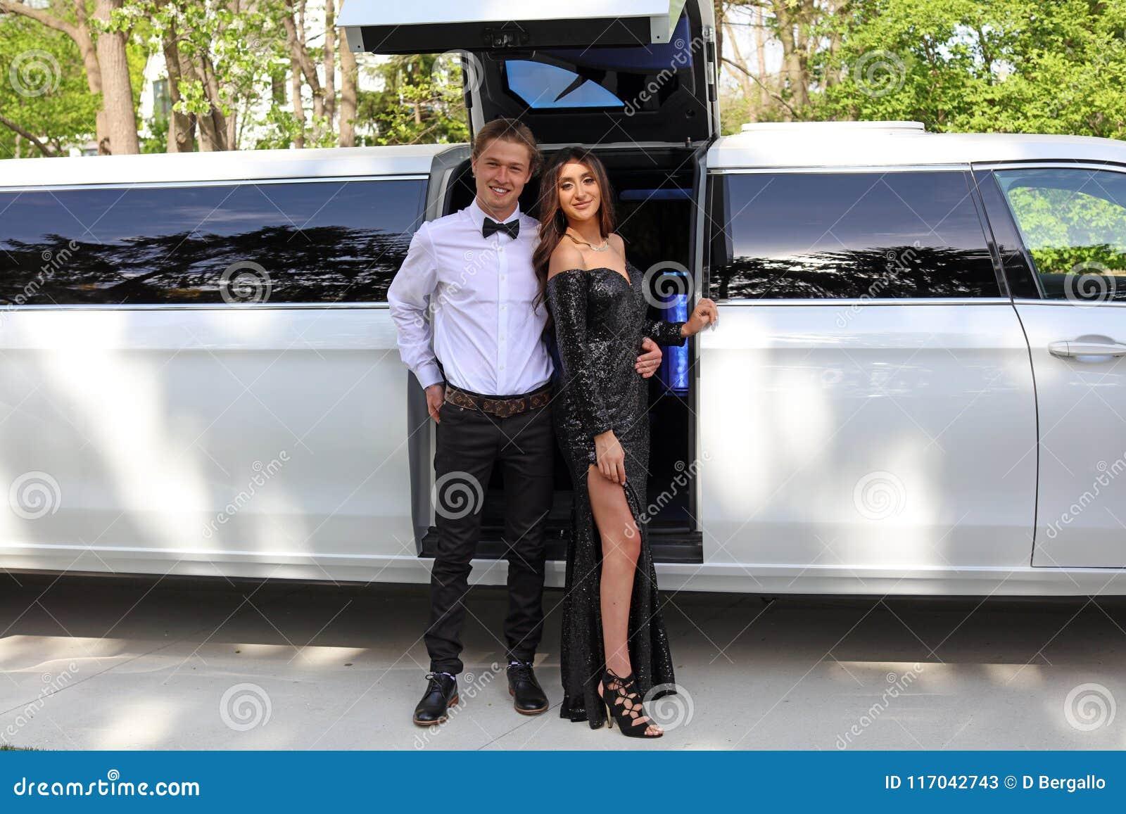Mulher bonita no vestido traseiro do baile de finalistas e indivíduo considerável no terno, adolescente  sexy  pronto por uma noi