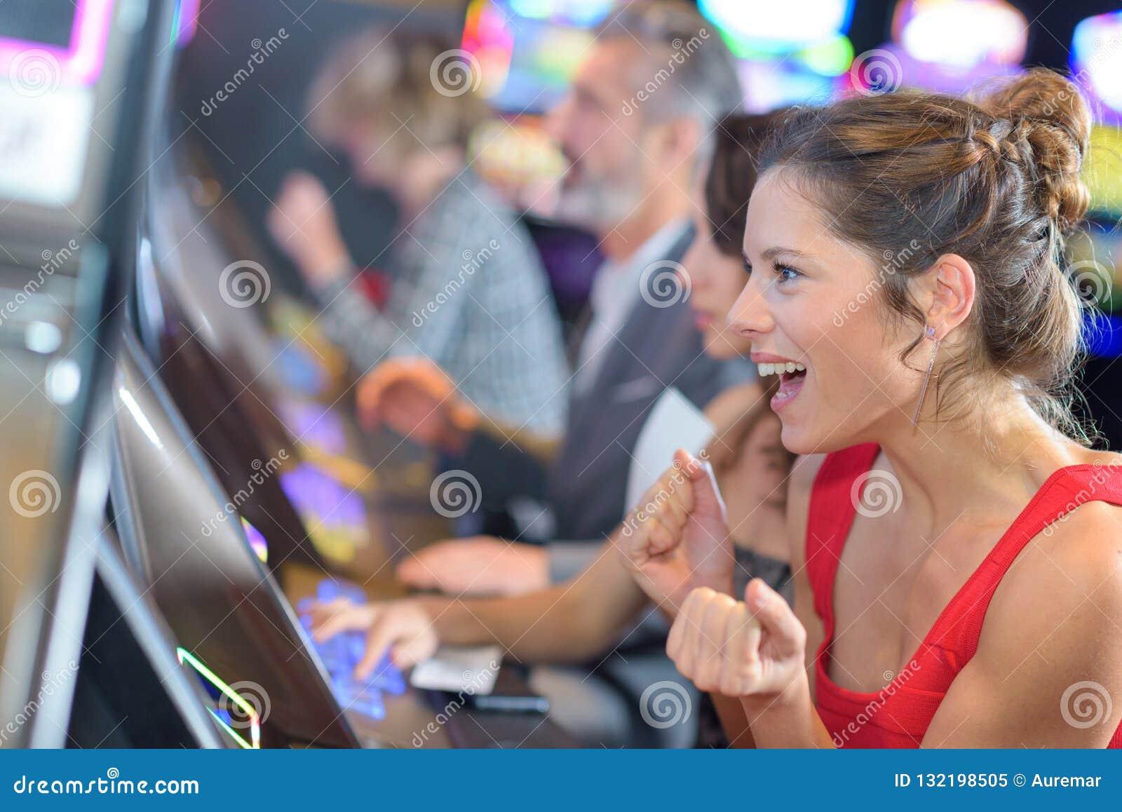 Mulher bonita no vestido vermelho que joga o slot machine