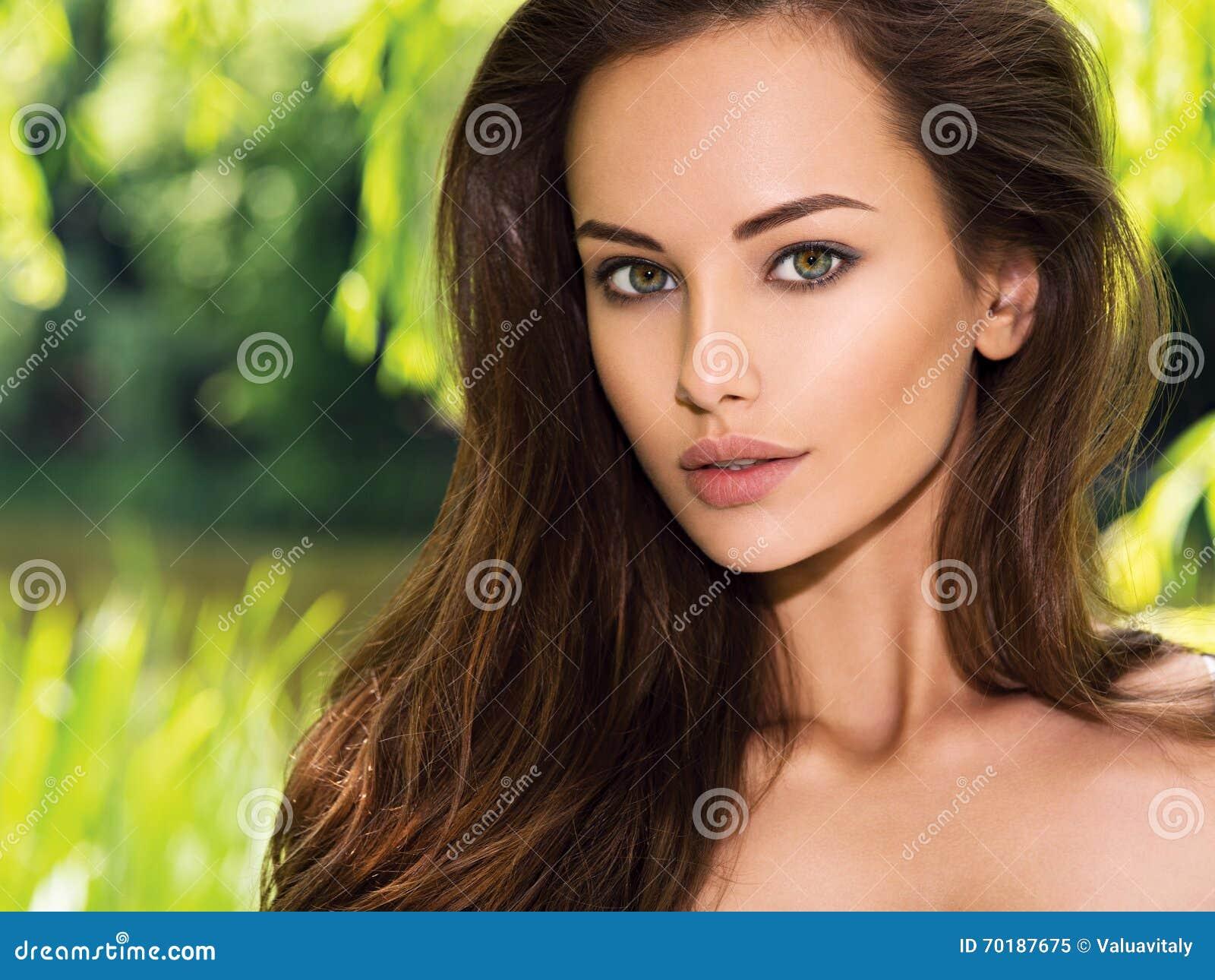 Mulher bonita nova com cabelos longos outdoors