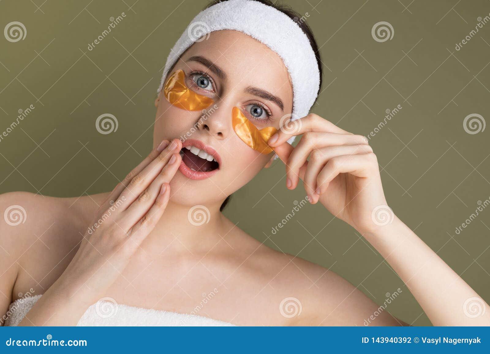 A mulher bonita nova com natural compõe a remoção do remendo do ouro de debaixo de seu olho