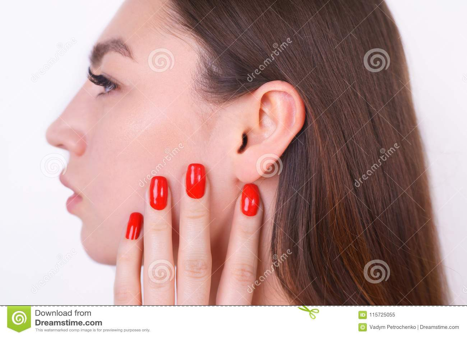 Mulher bonita nova com a pele perfeita que toca em sua orelha cosmet