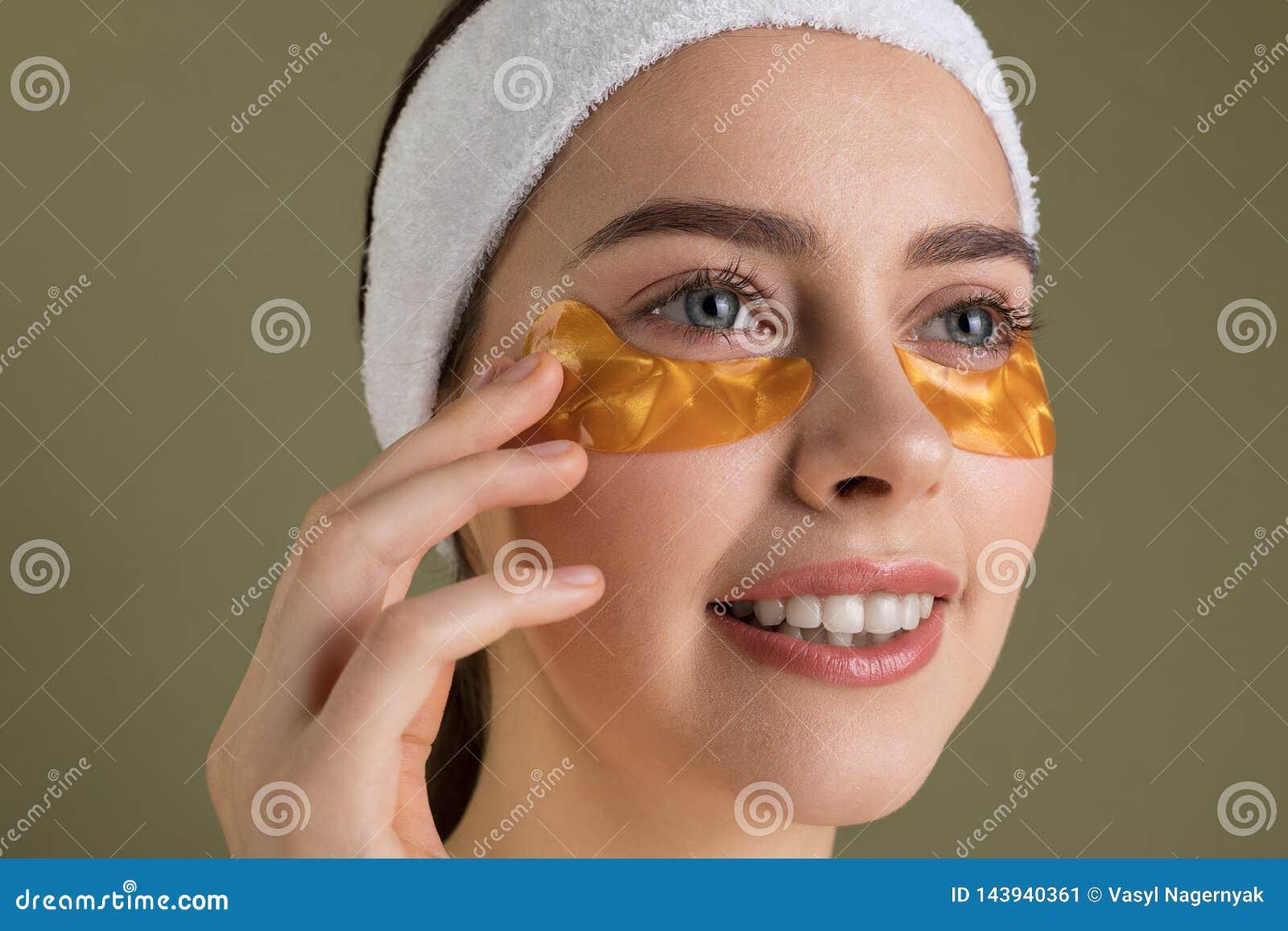 Mulher bonita nova de sorriso em remendos do ouro para os olhos no fundo verde