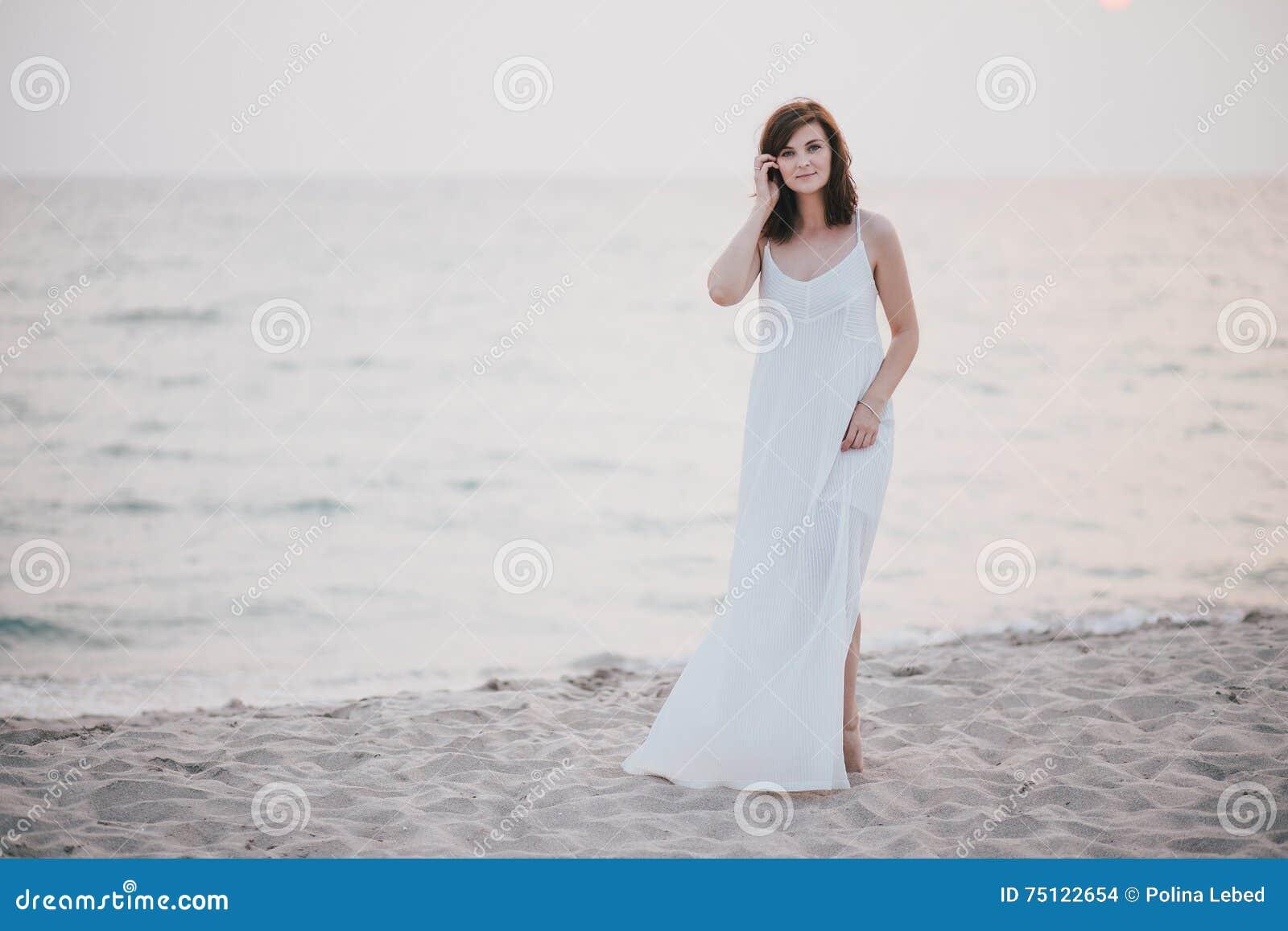 Mulher bonita nova em um vestido branco que anda em uma praia vazia perto do oceano