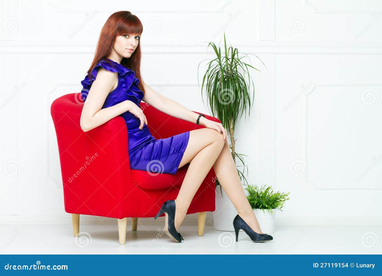 Mulher bonita nova em uma cadeira vermelha
