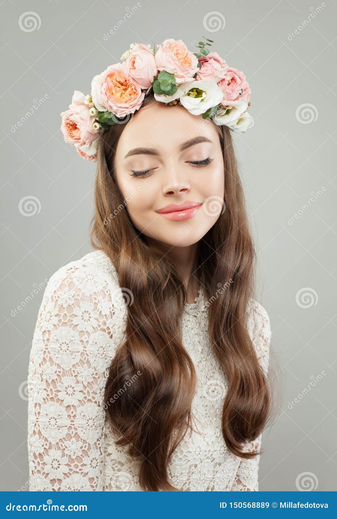 Mulher bonita nova Menina modelo bonita com a pele clara, cabelo brilhante longo e flores relaxando
