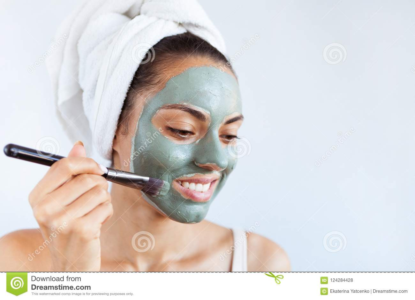Mulher bonita nova na máscara protetora da lama azul terapêutica Termas