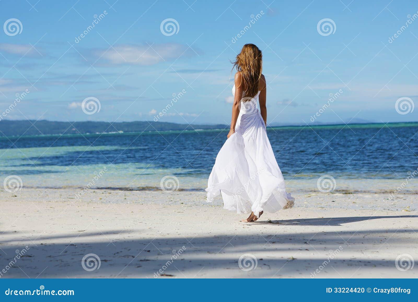Mulher bonita nova no vestido de casamento na praia tropical