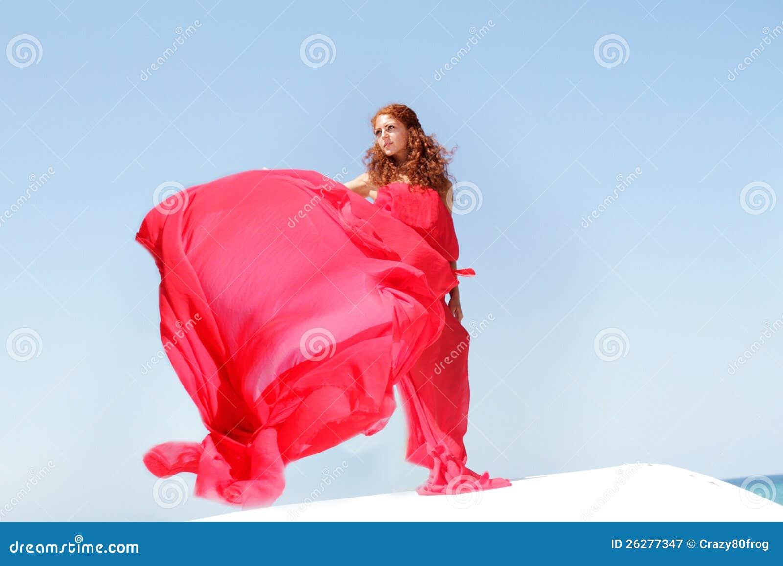 Mulher bonita nova no vestido vermelho sobre bly o céu