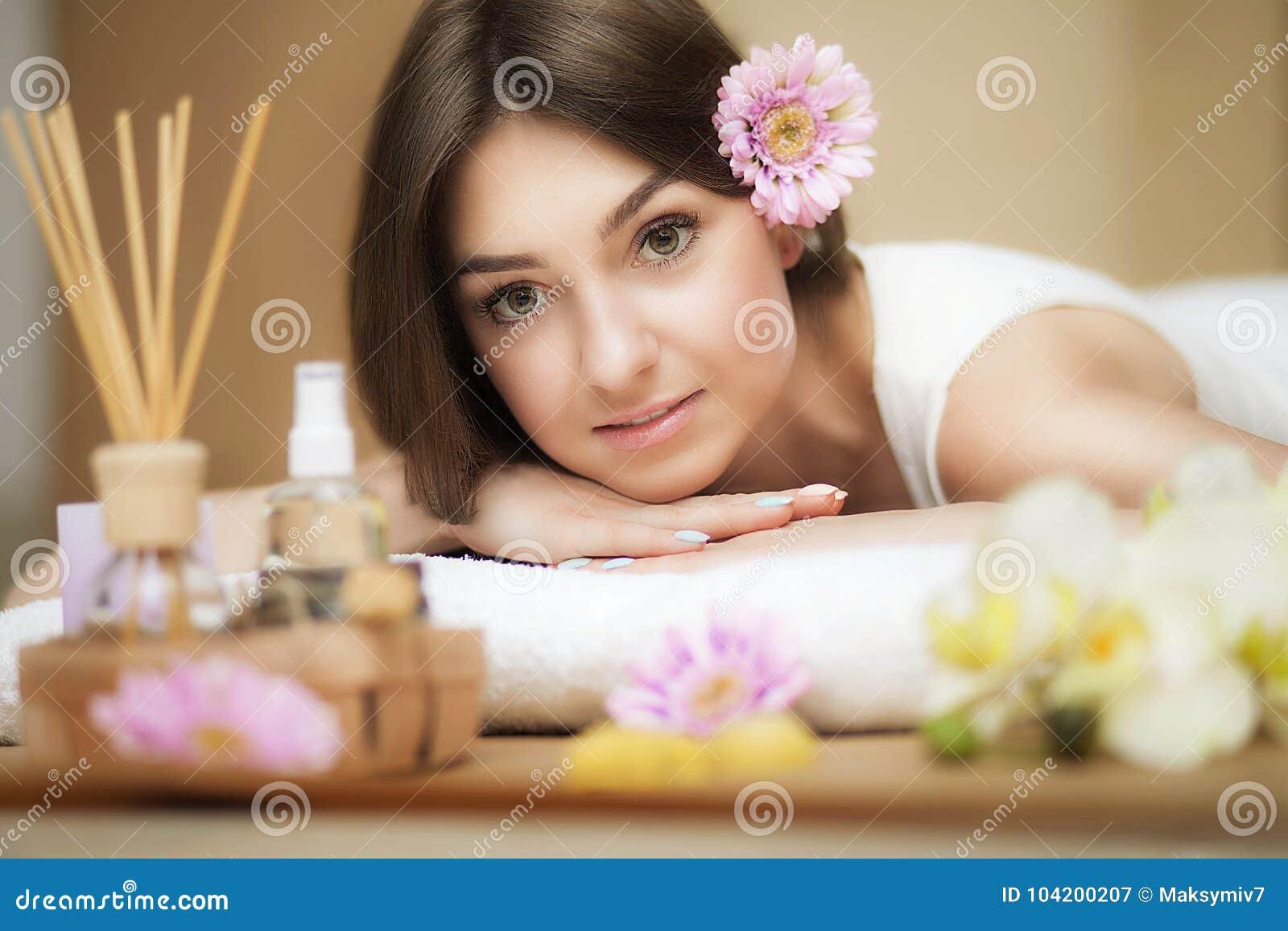 Mulher bonita nova nos termas Óleo e manteiga do aroma Olhar agradável O conceito da saúde e da beleza Melhore no salão de beleza