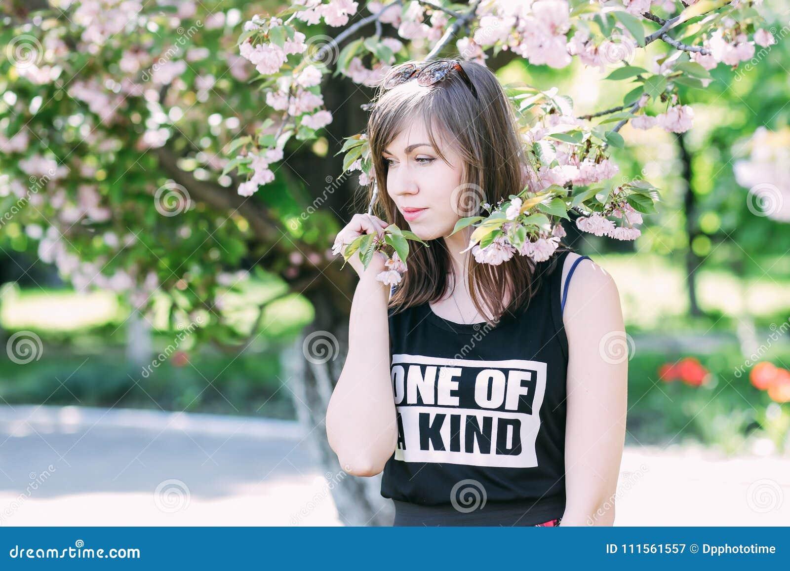 Mulher bonita nova perto da árvore de florescência de sakura Flores, mola e conceito cor-de-rosa da juventude Menina à moda