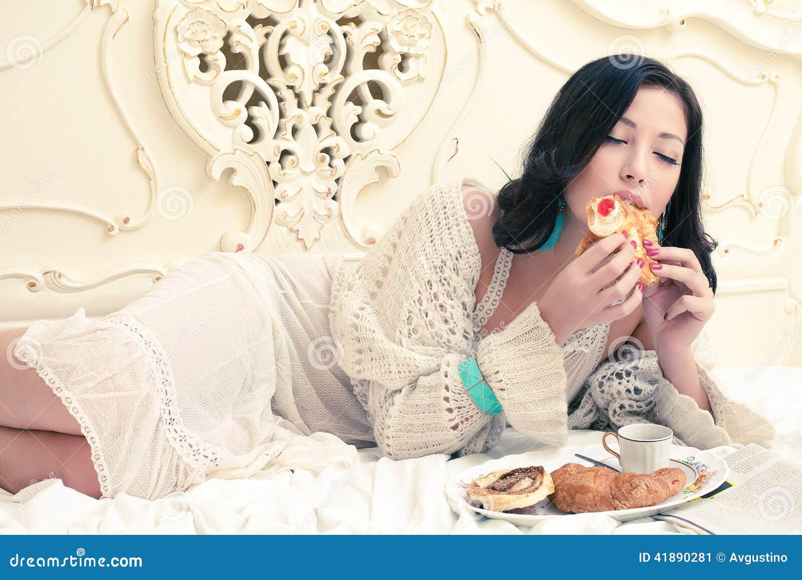 Mulher bonita nova que come o croissant com doce