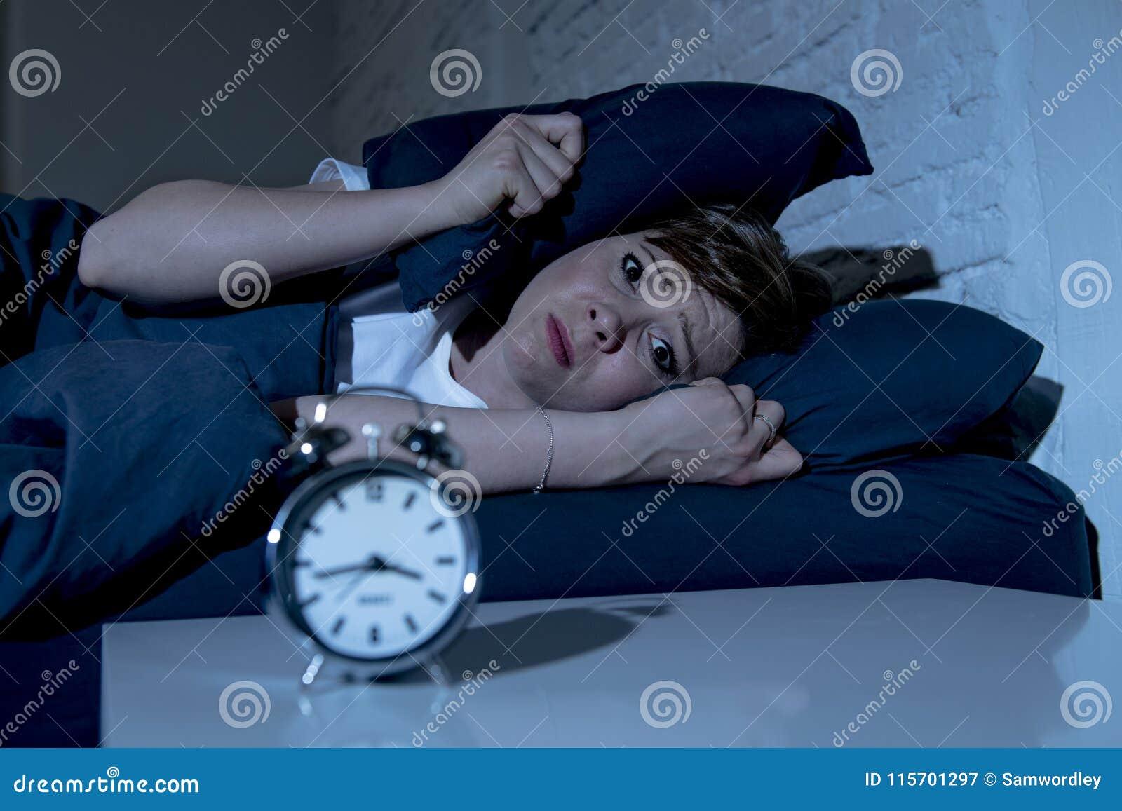 Mulher bonita nova que encontra-se na cama tarde na noite que sofre da insônia que tenta dormir