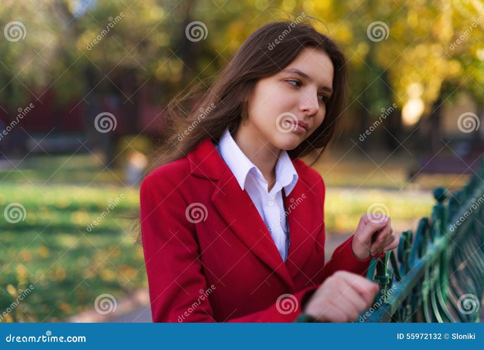 Mulher bonita nova que está no parque do outono