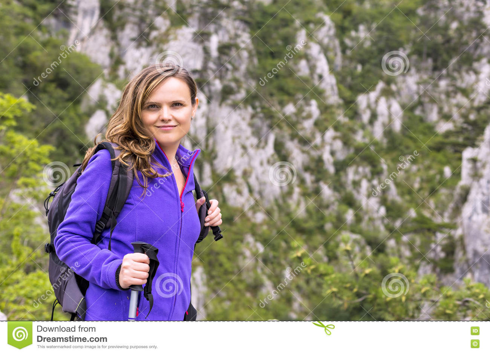 Mulher bonita nova que guarda a caminhada do polo ao escalar o ro