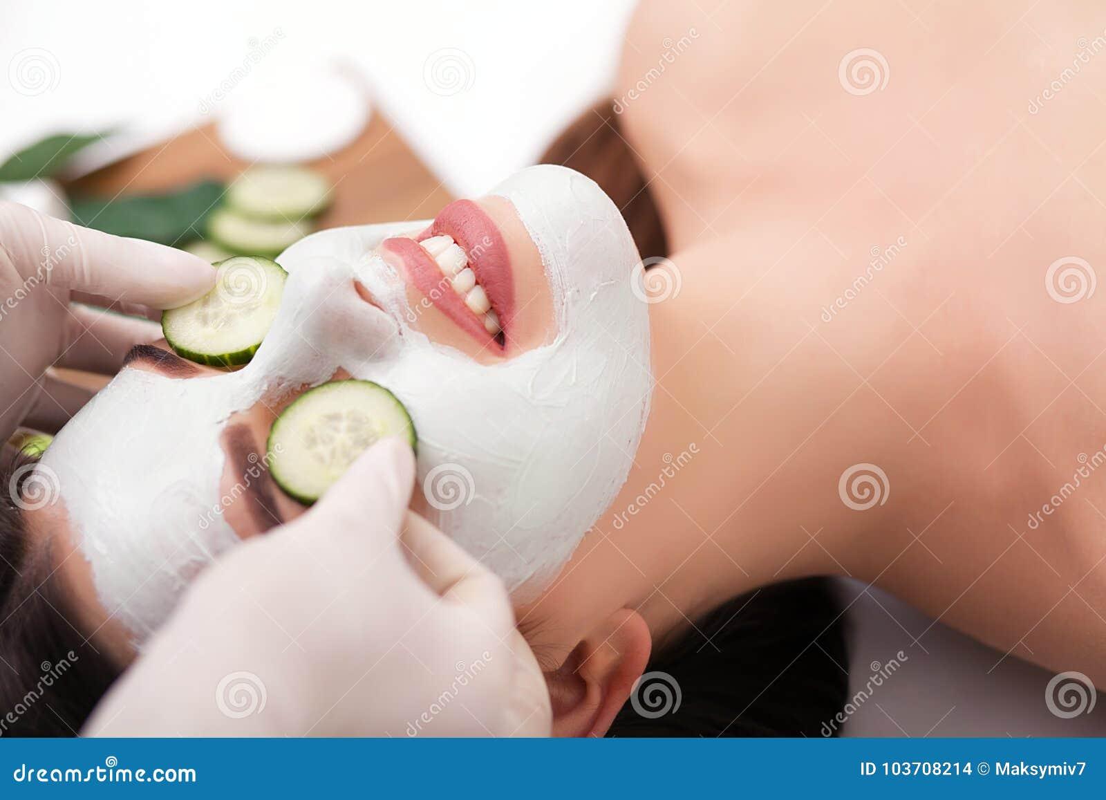 Mulher bonita nova que recebe a máscara facial da argila no salão de beleza dos termas Cuidados com a pele, tratamentos da beleza