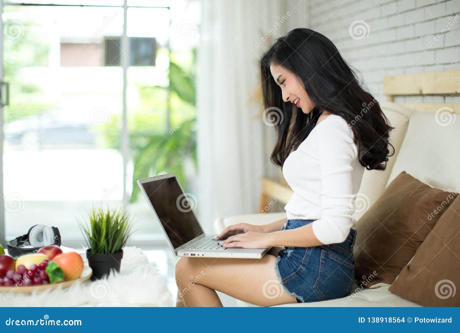 Mulher bonita nova que usa um laptop