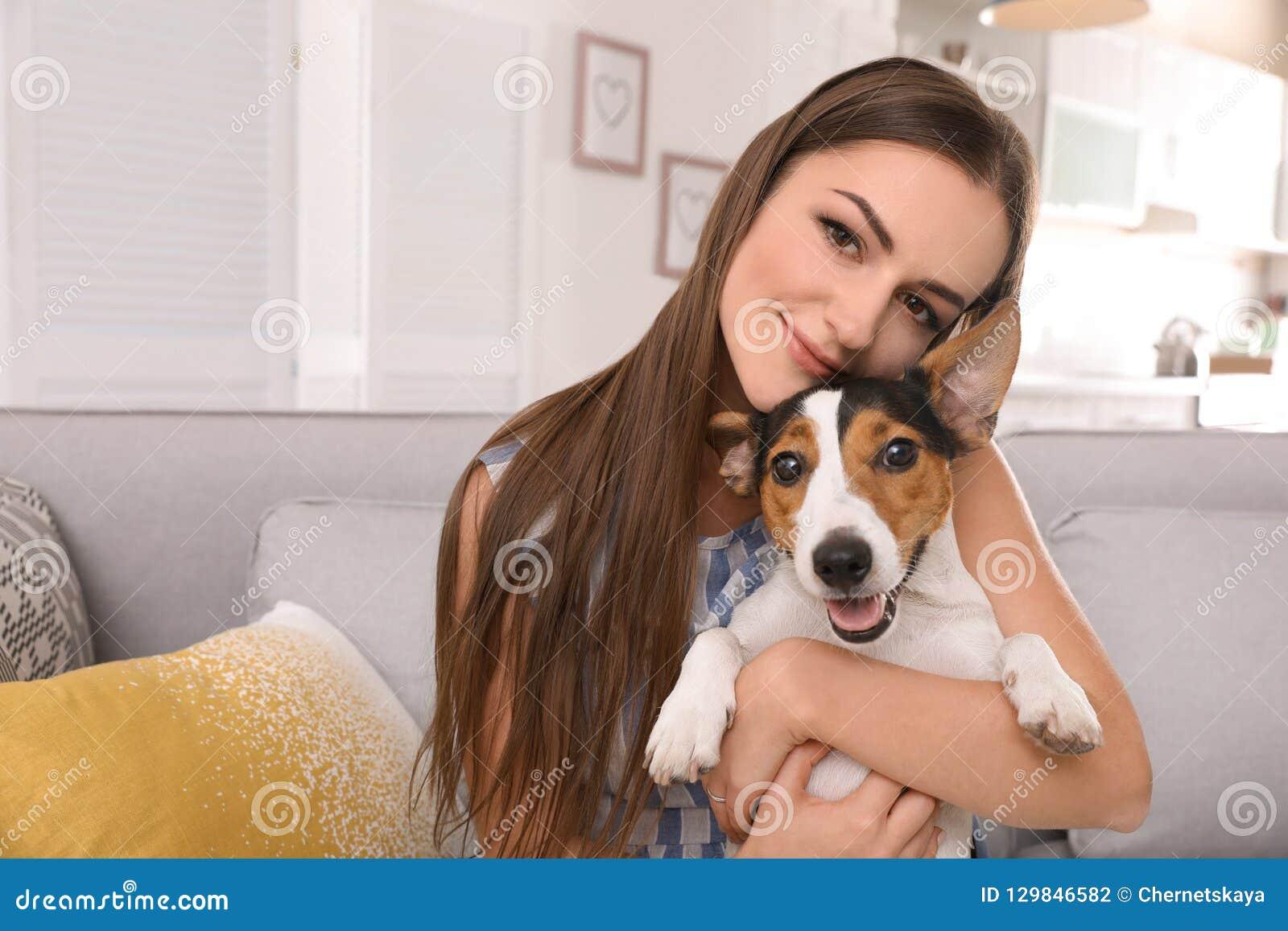 Mulher bonita que abraça seu cão no sofá