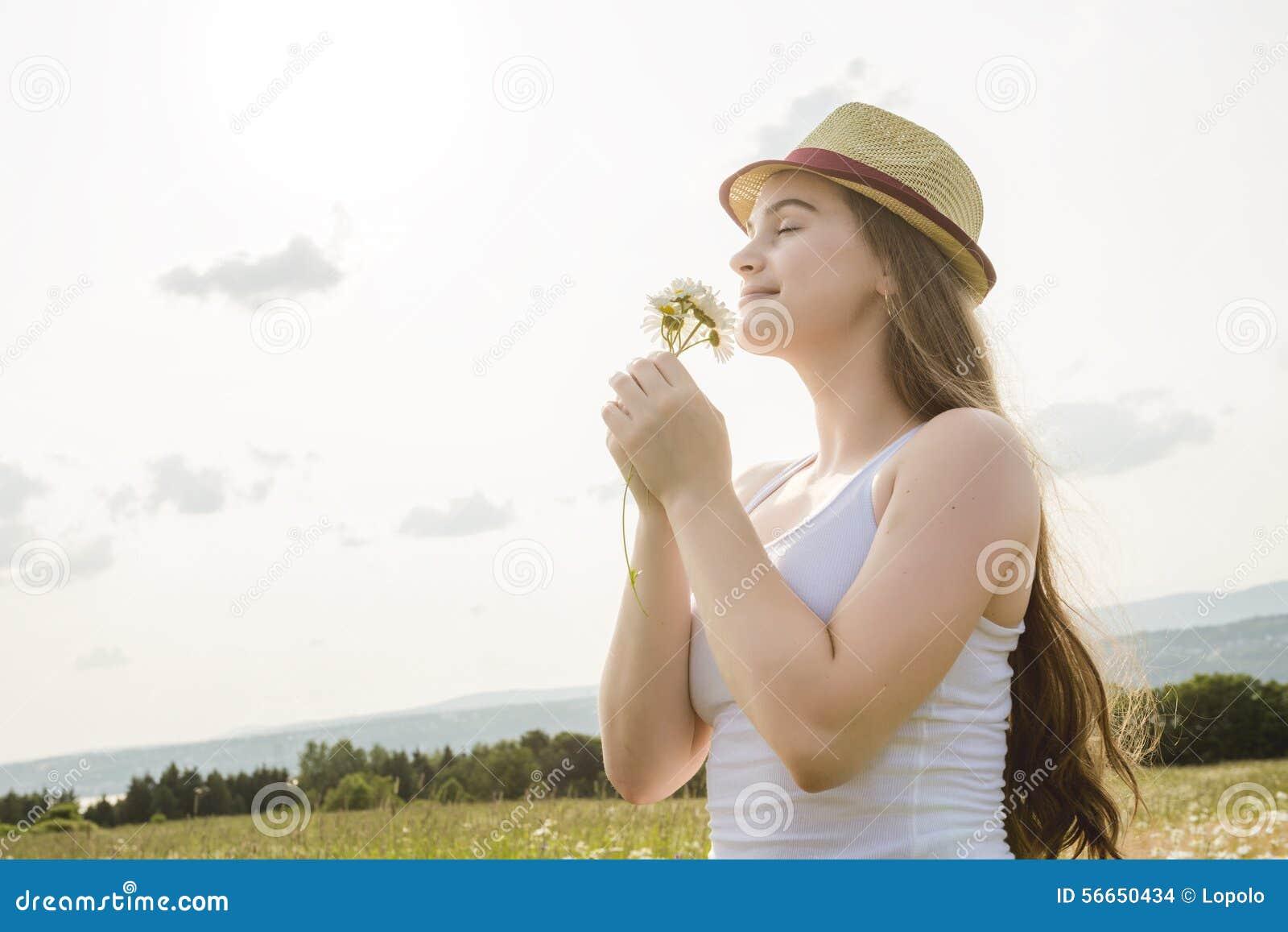 Mulher bonita que aprecia a margarida em um campo