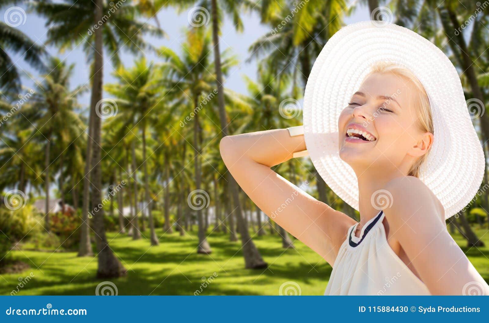 Mulher bonita que aprecia o verão sobre palmeiras