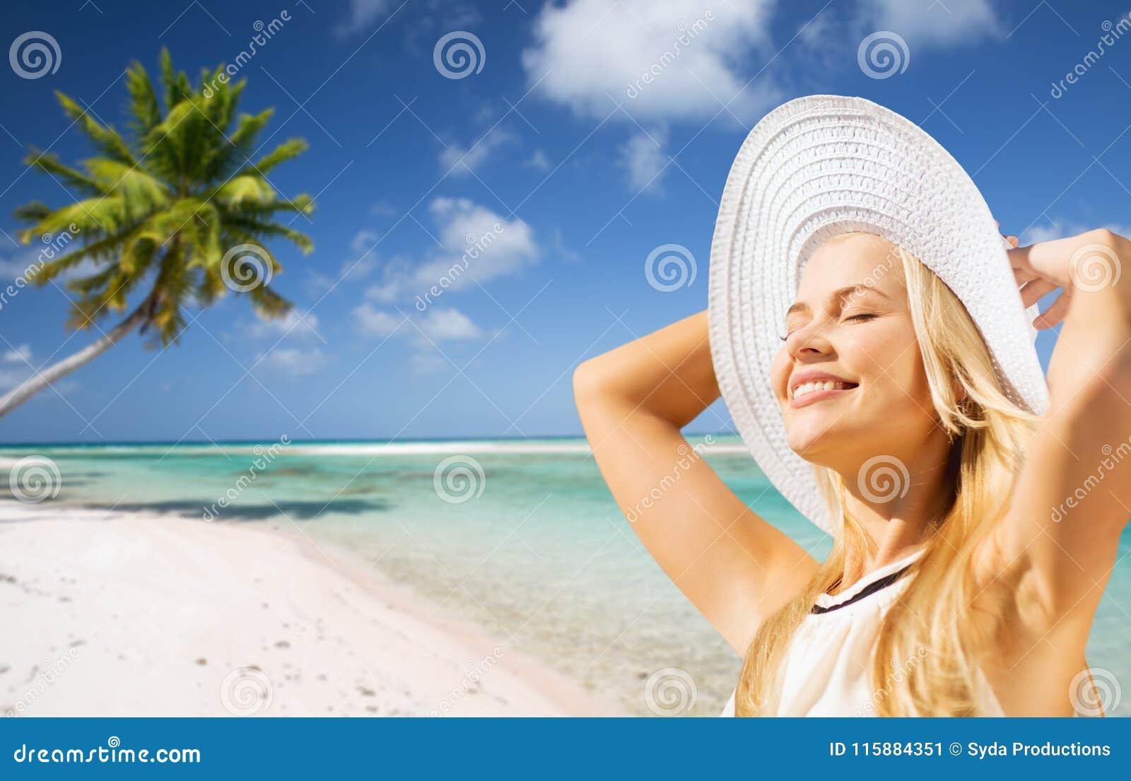 Mulher bonita que aprecia o verão sobre a praia