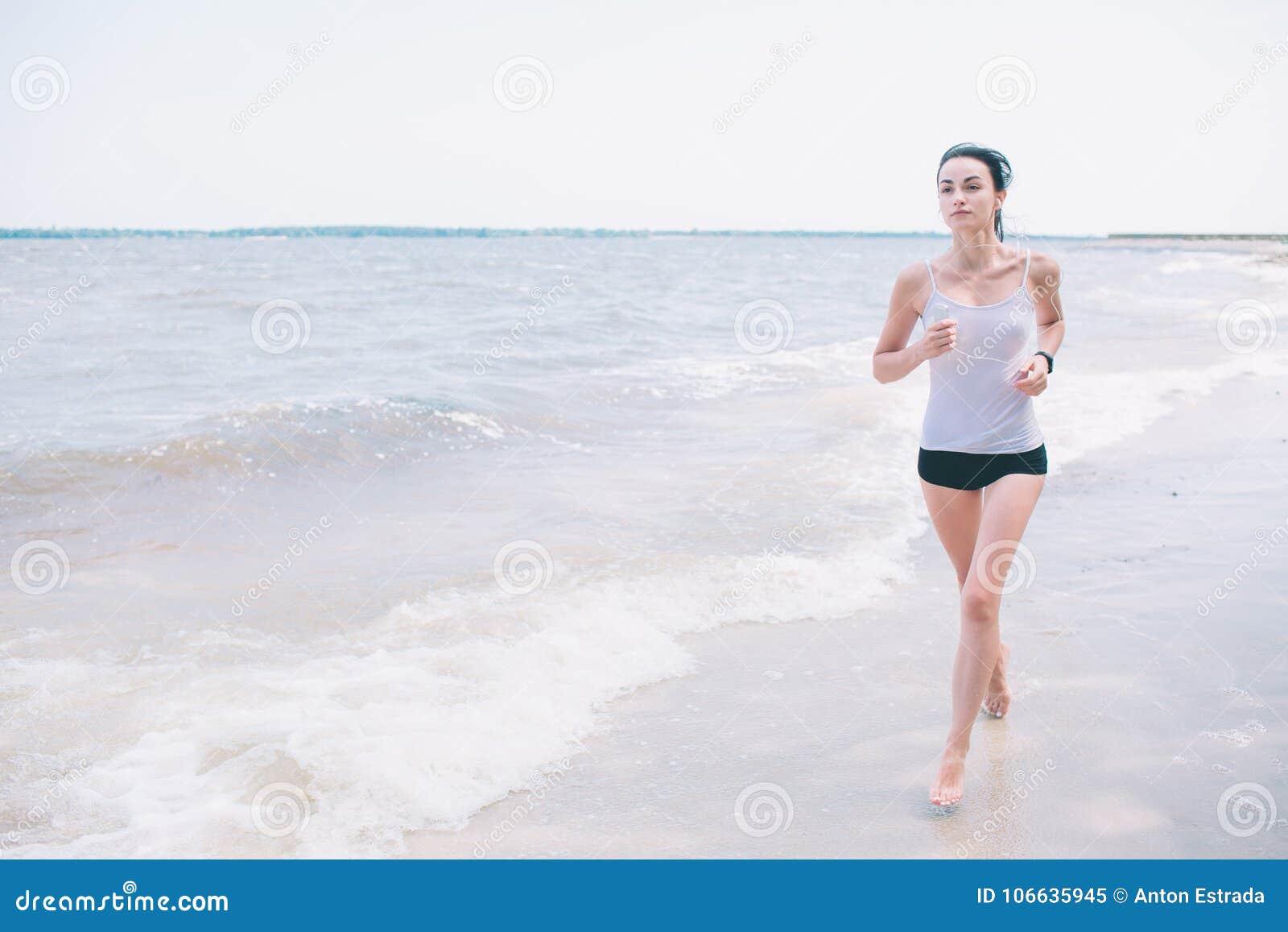 Mulher bonita que corre durante o por do sol Modelo novo da aptidão perto do beira-mar Vestido no sportswear