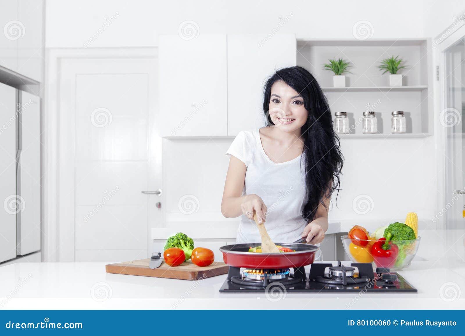 Mulher bonita que cozinha ao sorrir