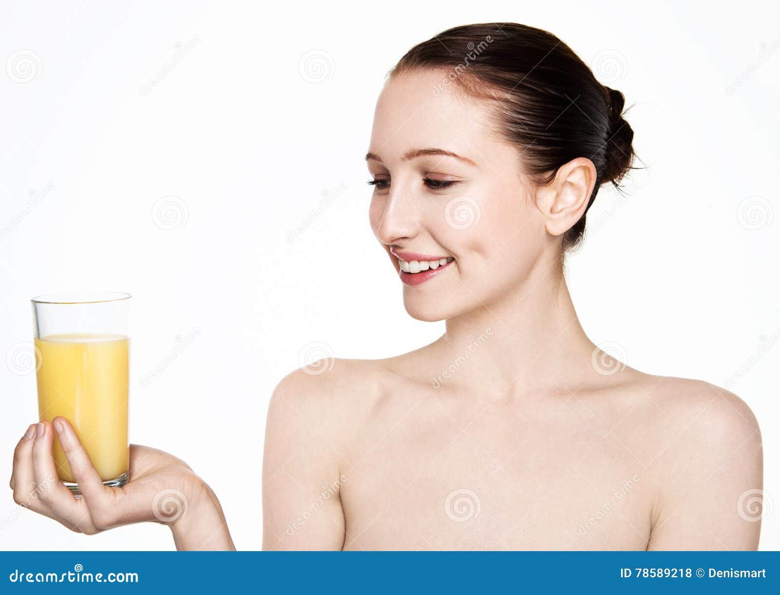 Mulher bonita que guarda de vidro com suco de laranja