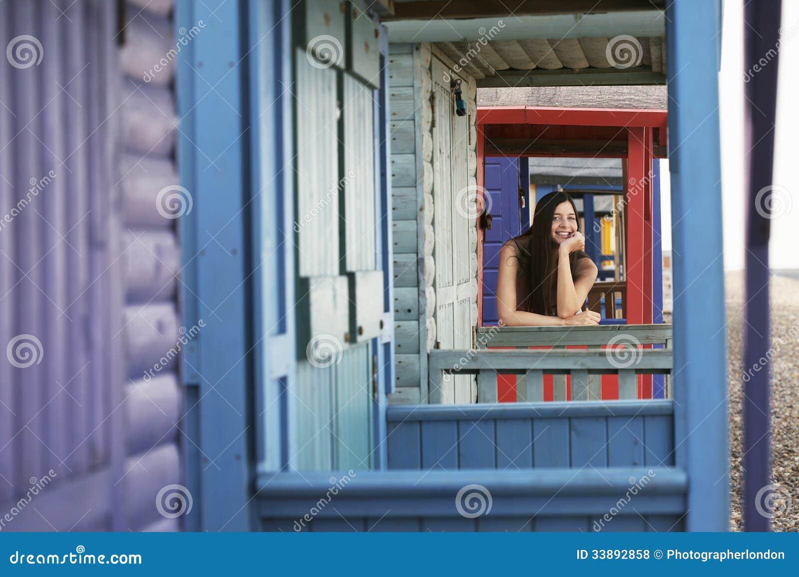 Mulher bonita que inclina-se na balaustrada da casa de praia