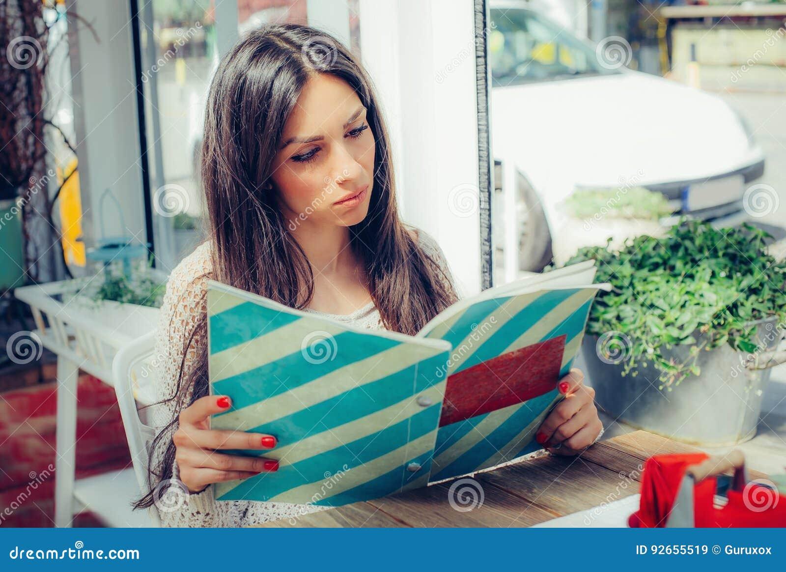 Mulher bonita que olha o menu e que pede alimentos no restaurante