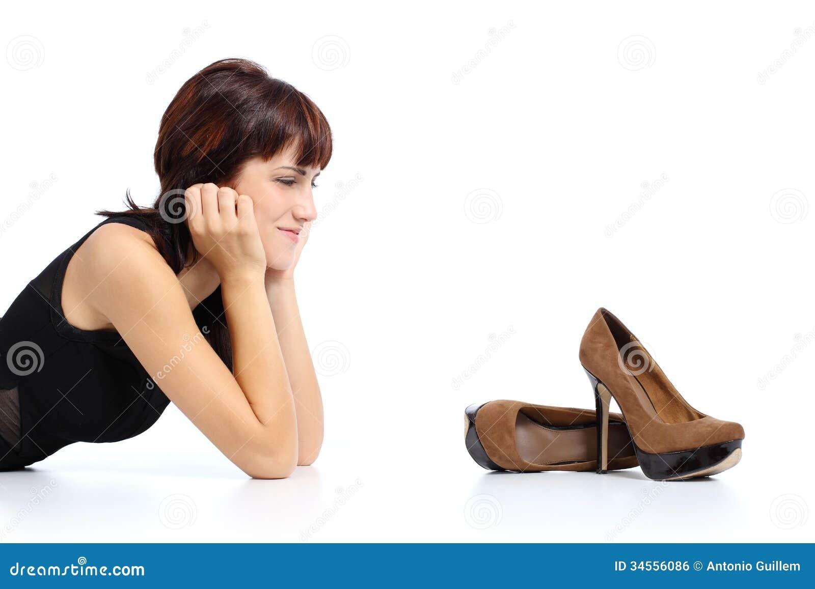 Mulher bonita que olha sapatas de um estilete dos saltos altos