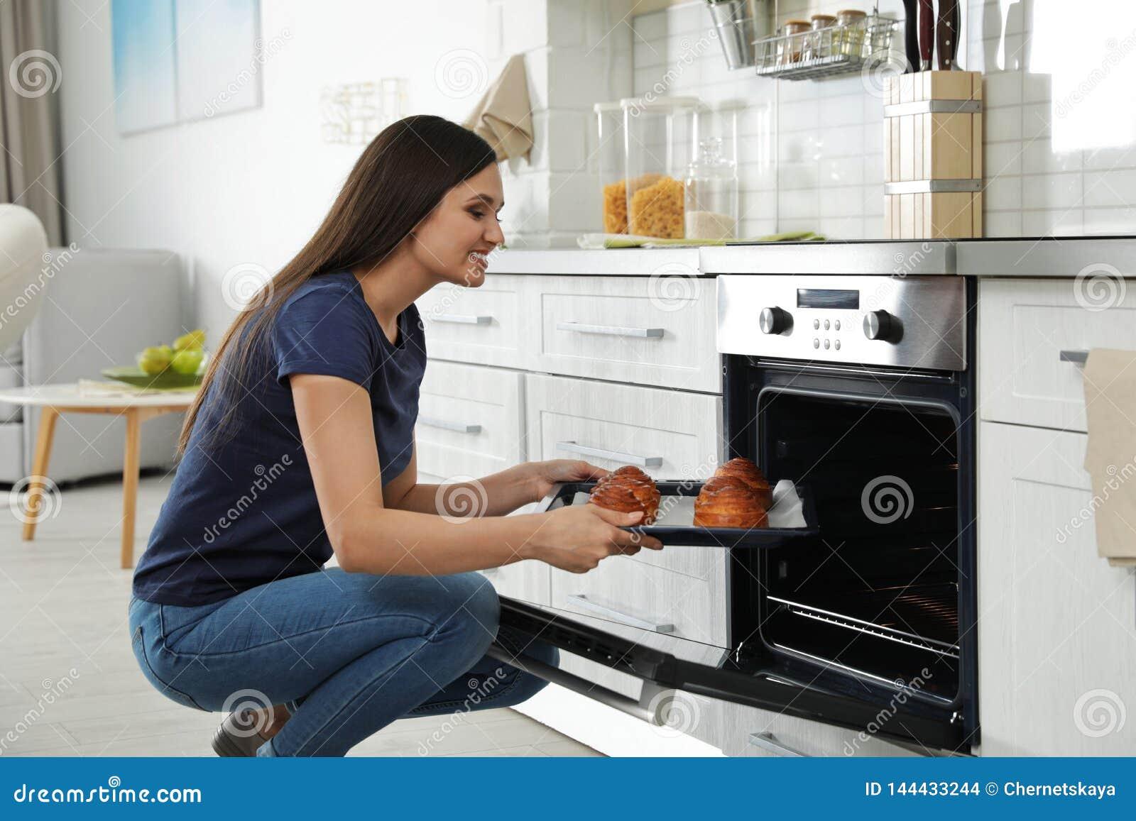 Mulher bonita que remove a bandeja de bolos cozidos do forno