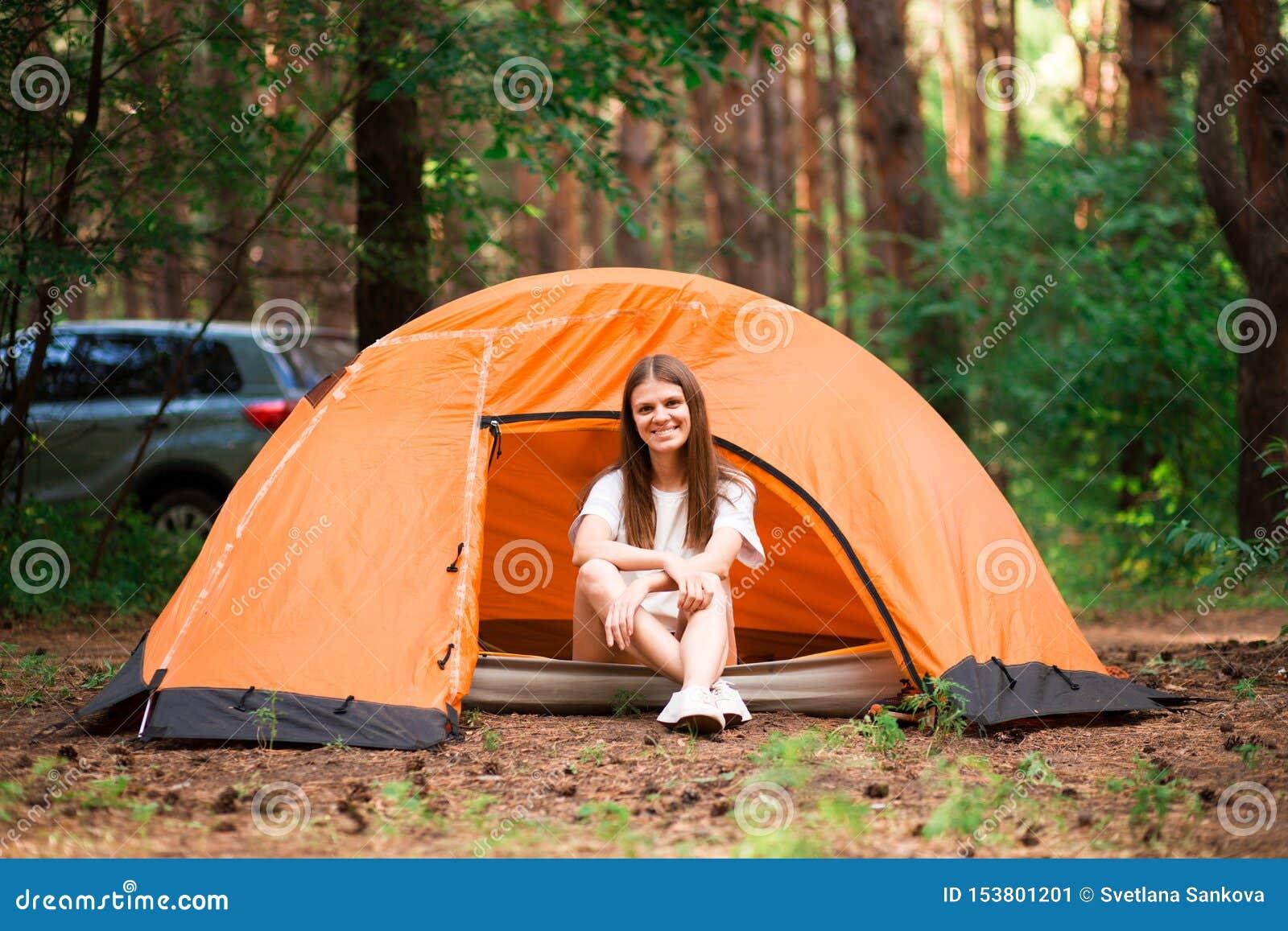 Mulher bonita que senta-se fora da barraca nas férias alternativas livres que acampam no estilo de vida diferente da floresta
