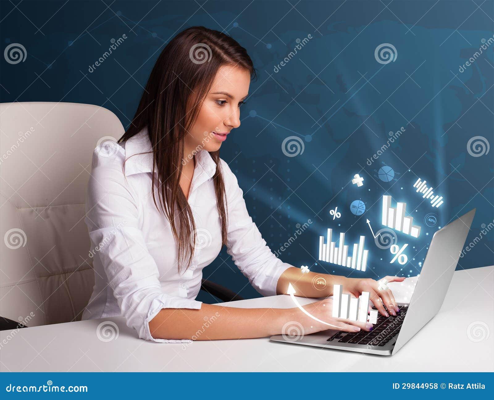 Mulher bonita que senta-se na mesa e que datilografa no portátil com diagramas