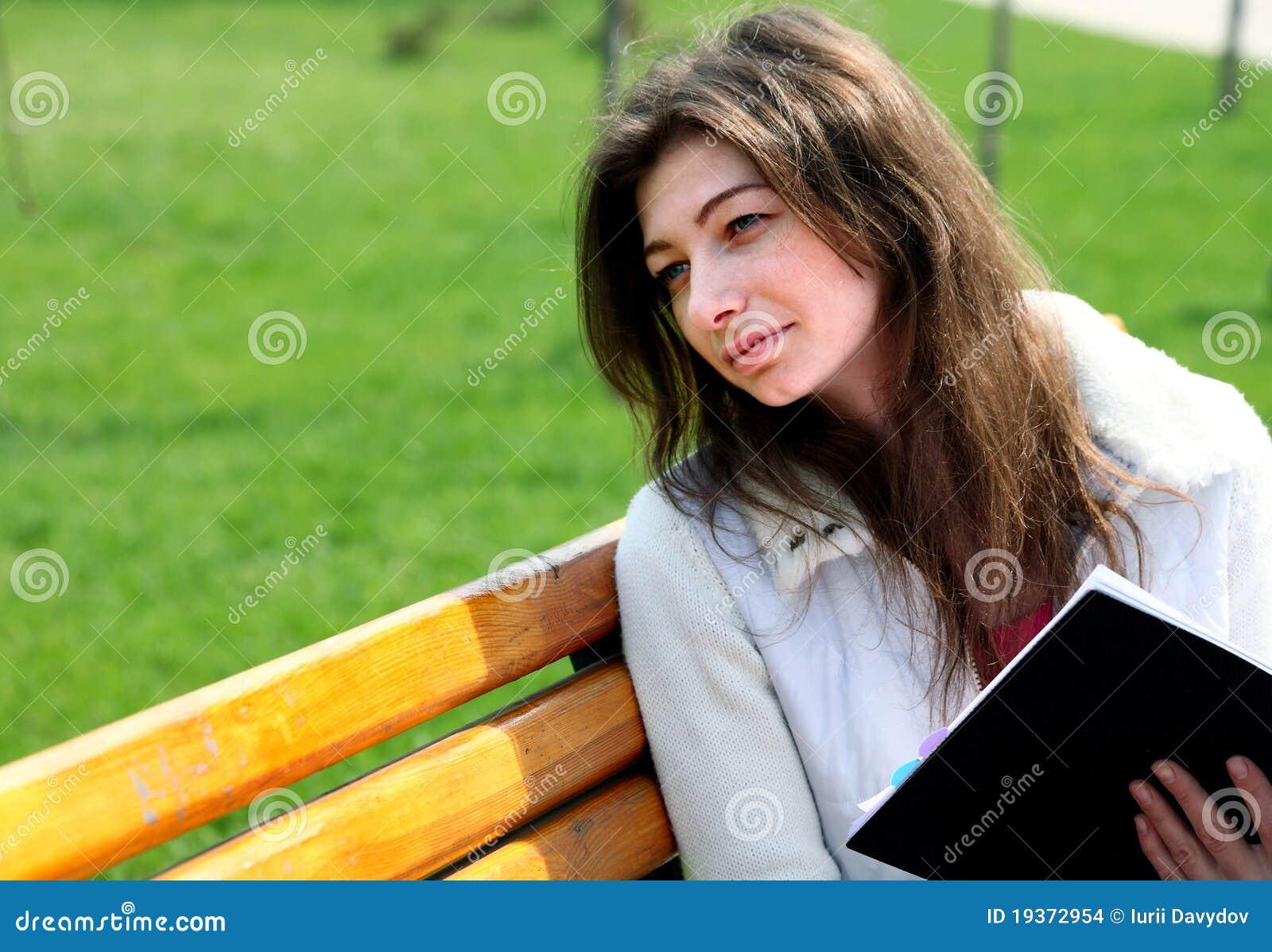 Mulher bonita que senta-se no banco no livro de leitura do parque