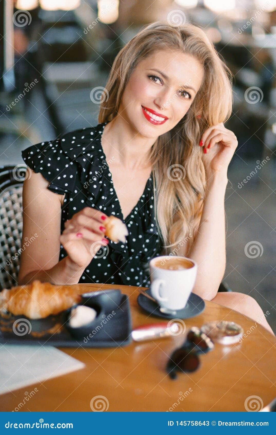 Mulher bonita que senta-se no caf?
