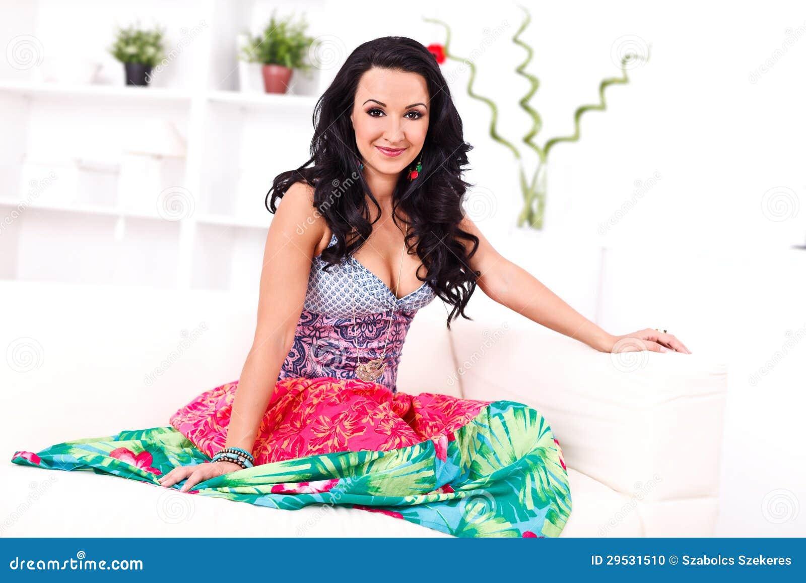Mulher bonita que senta-se no sofá